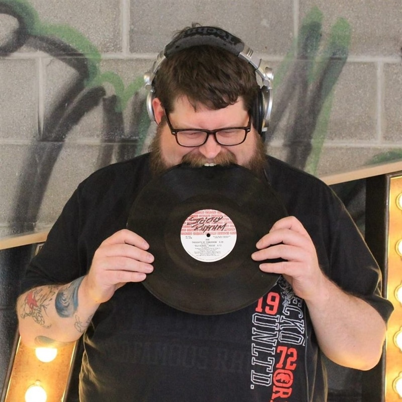 Image of Team Member Norm biting into a record.