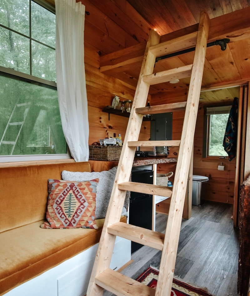 Tiny home, cozy room layout with ladder to upstairs.