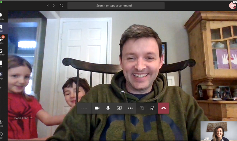 Image of Colin video chatting team members with kids in background