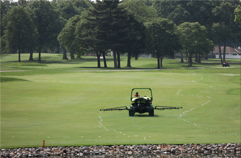 Image of lawn care employee spreading fertilizer out on turf.