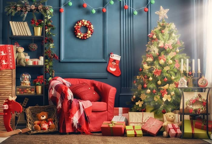 Bright red chair with holiday decorations and a Christmas tree