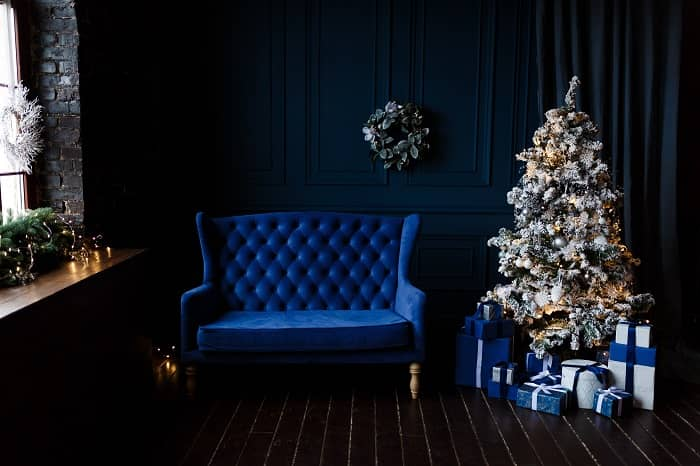 Blue room with navy velvet loveseat and a Christmas tree