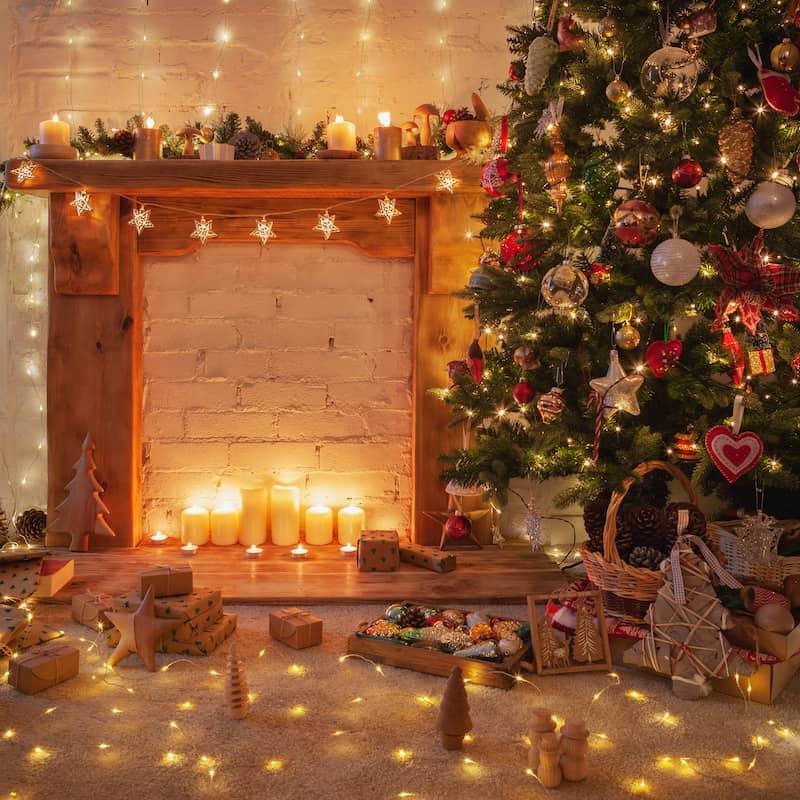 Christmas tree next to wood fireplace on a white brick wall