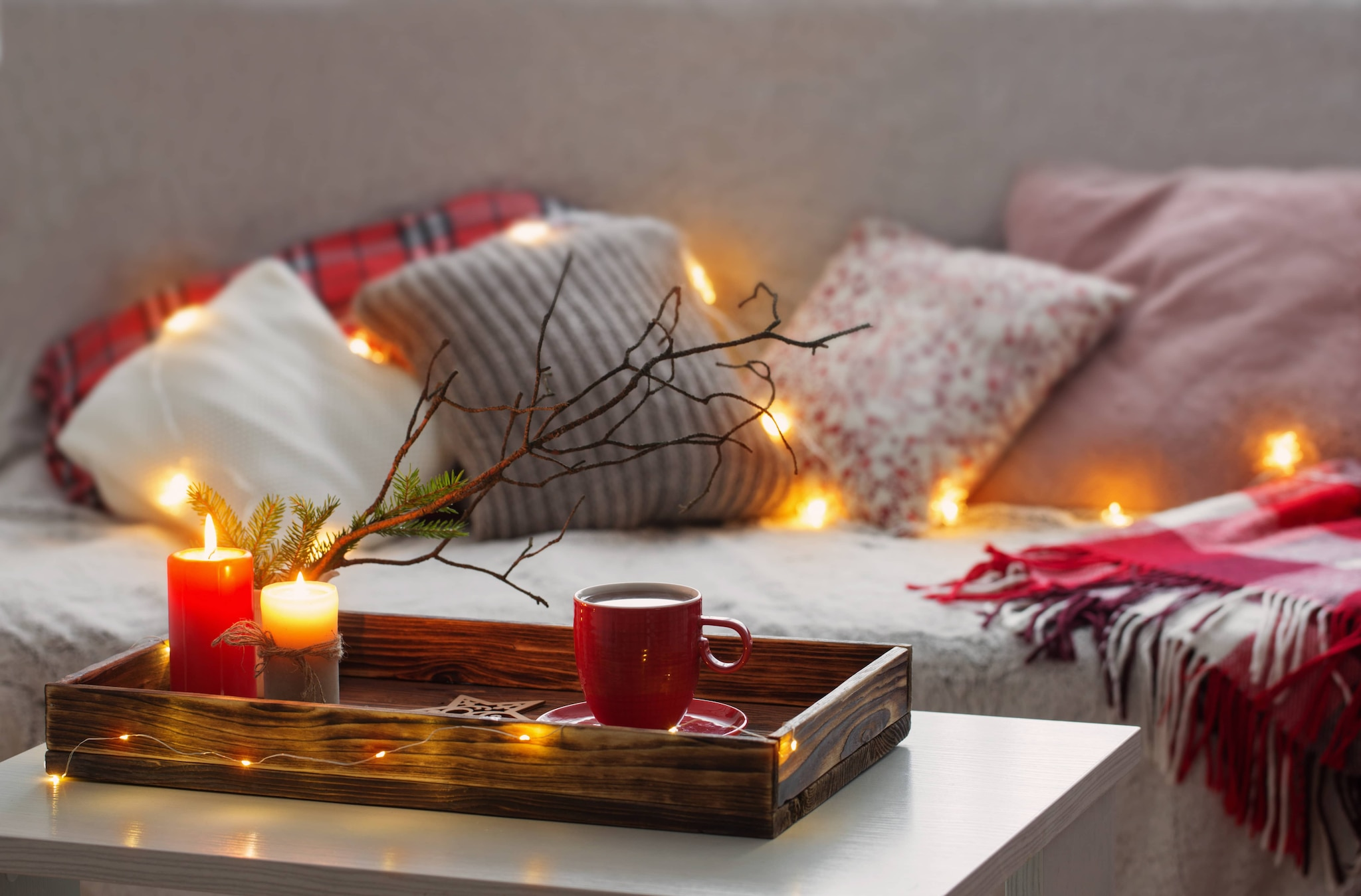 cozy couch with red cup in a tray on the coffee table