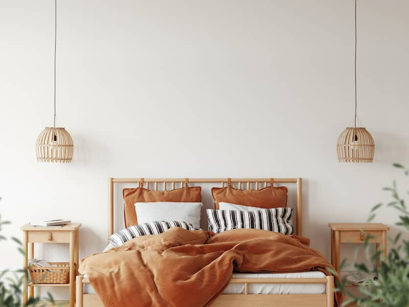 Boho bedroom with orange bedding and wicker lamps.