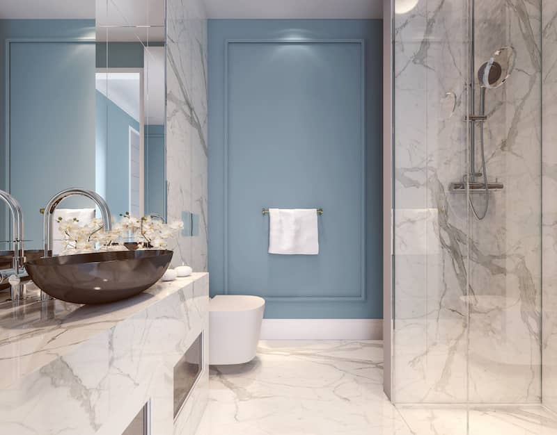 Blue accent wall in an all white marble bathroom