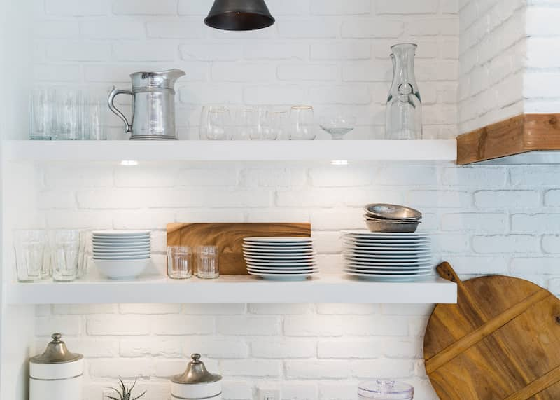 White kitchen with exposed shelving nicely organzied