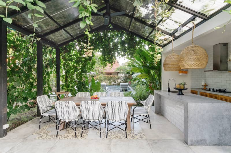 outdoor kitchen covered over with greenery and screened awning
