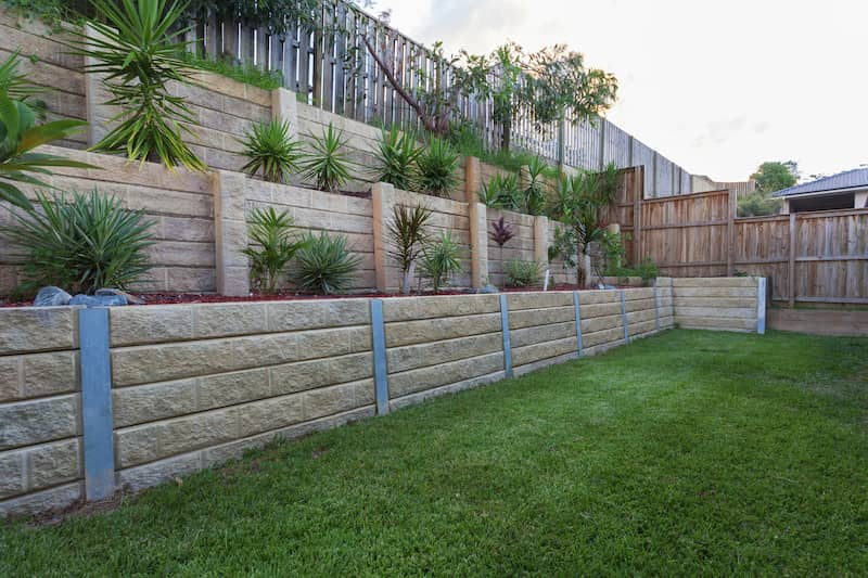 two retaining walls in backyard stacked above each other with plants filling them