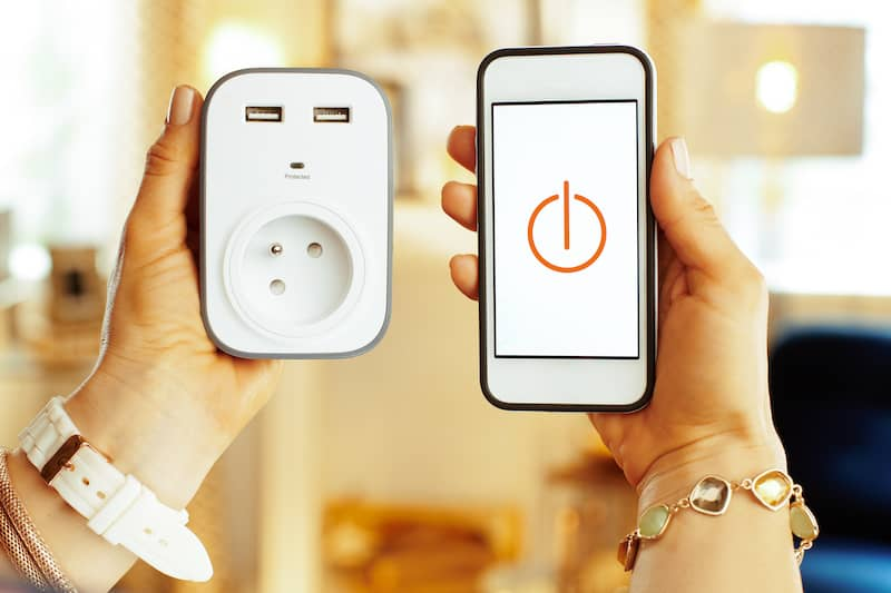 person holding smart phone and tech plug in