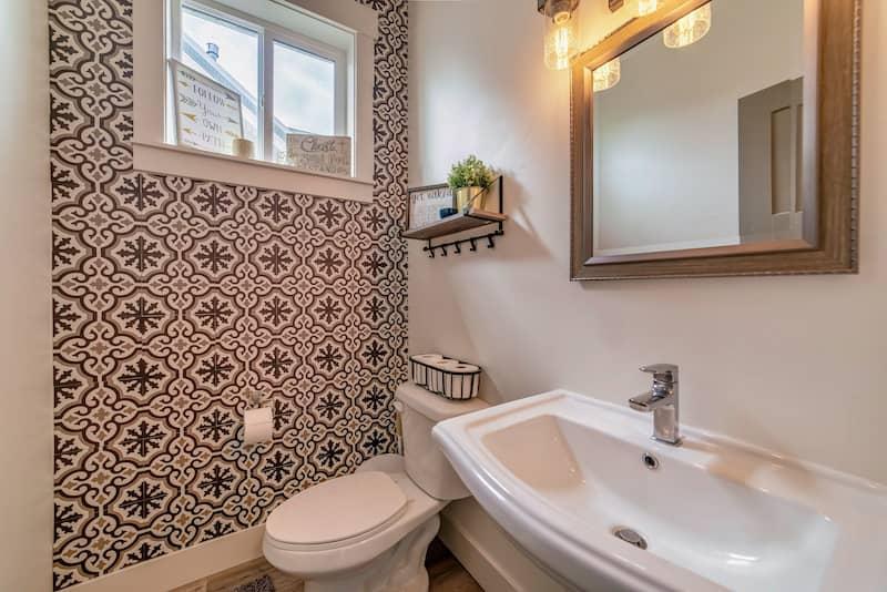 printed wallpaper on far wall of small bathroom