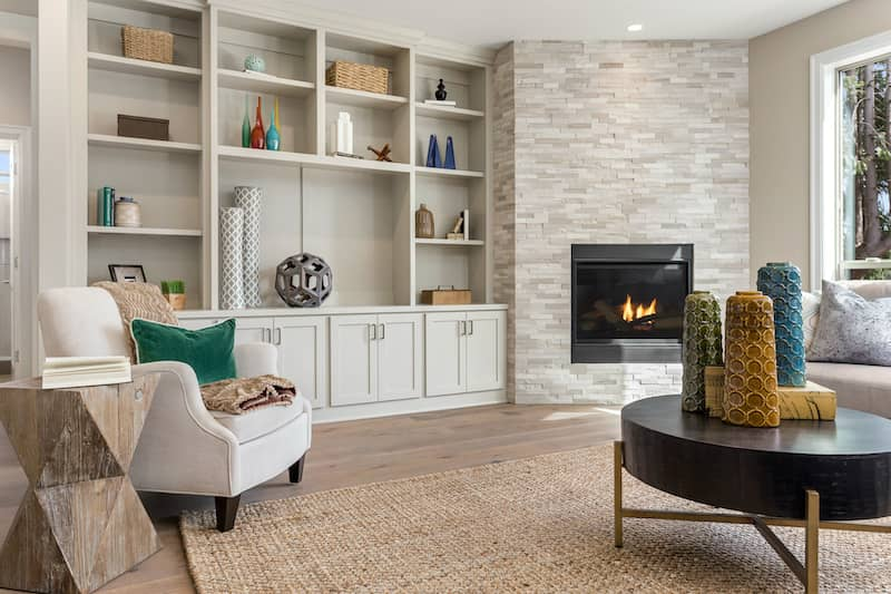 living room with showcase wall with built-in bookshelf and fireplace