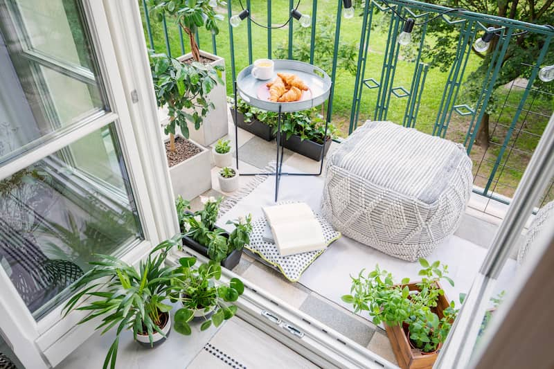 top view of a balcony with plants pouf a table with breakfast