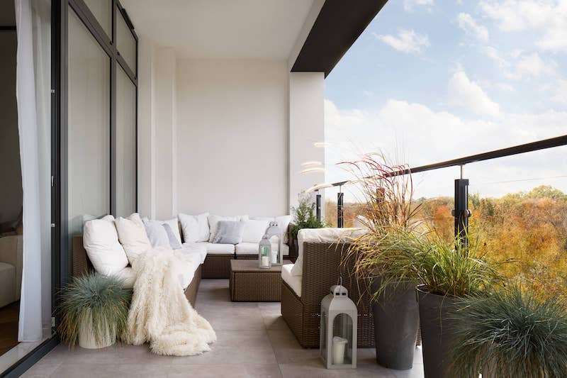 elegant decorated balcony with rattan outdoor furniture bright pillows and plants