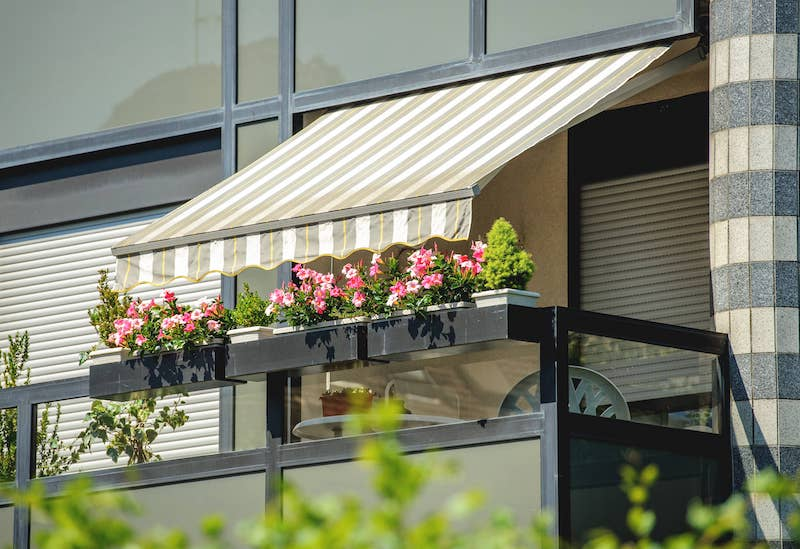 balcony with awning opened and beautiful flowers covered by sun shield on a warm summer day