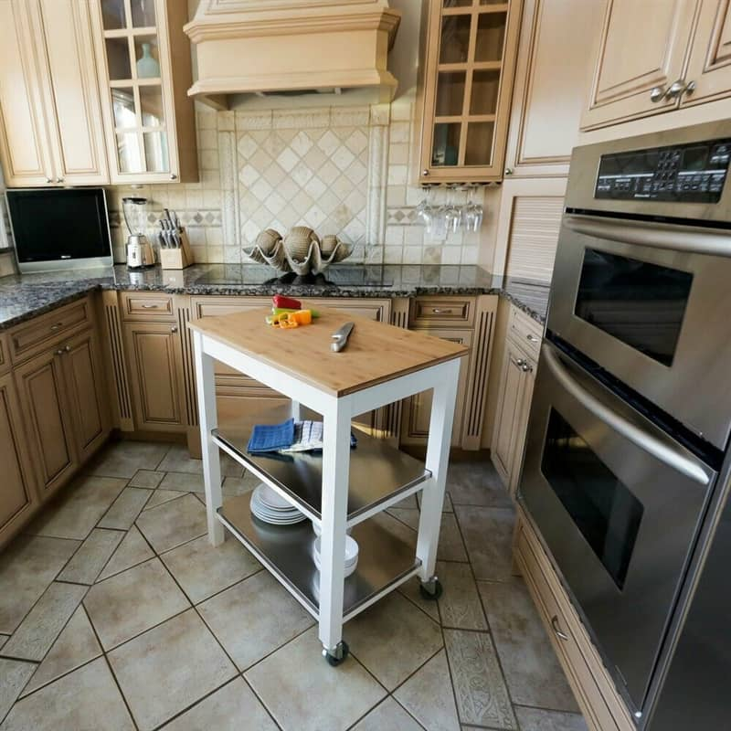 A shelf on wheels with a butcher block top in a kitchen.