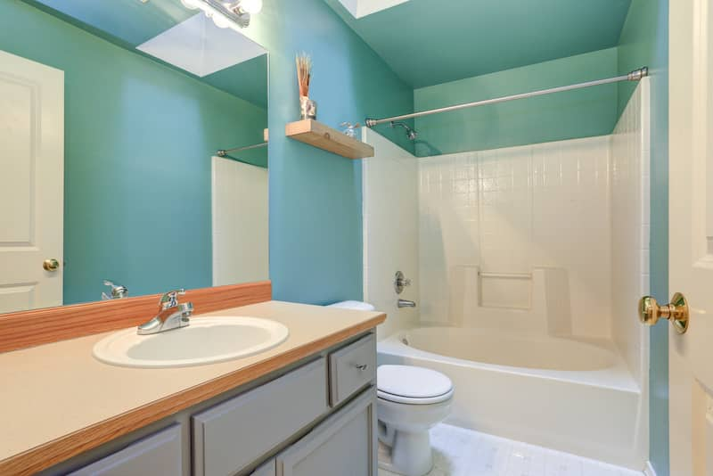 Bathtub/shower combo in common bathroom with blue walls and white counters