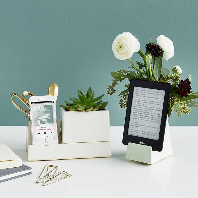 Smart devices on a desk with flowers in a vase connected to the device stands.