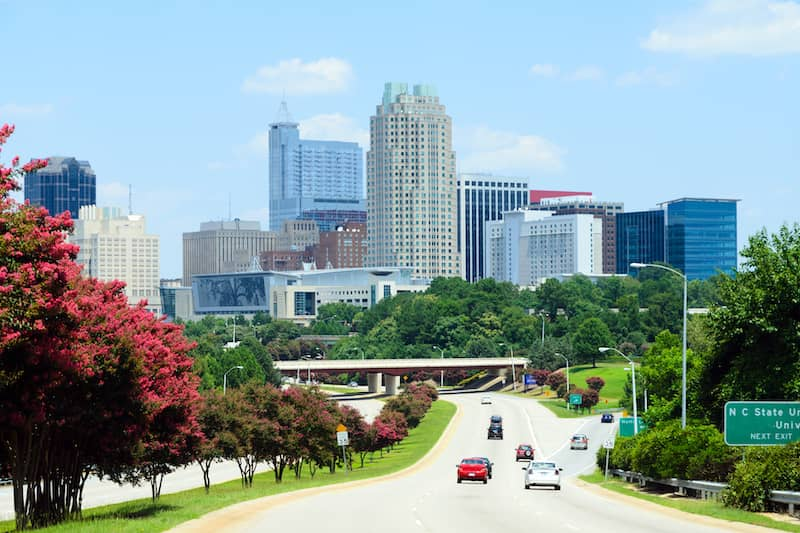 view of Raleigh driving towards downtown with red flowers along road