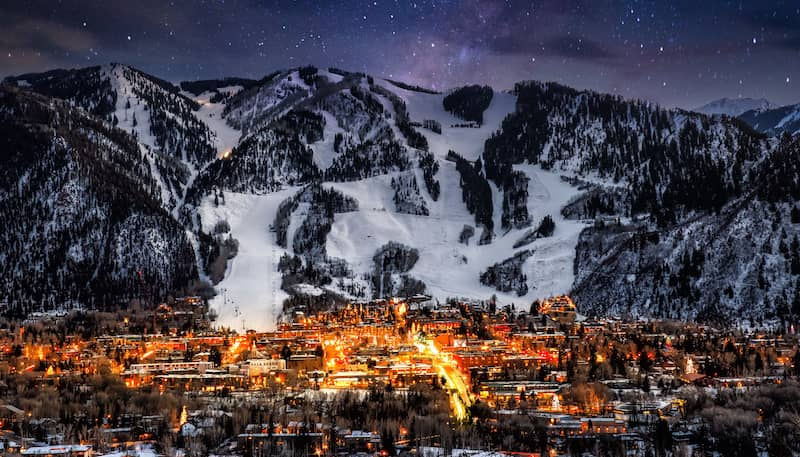city at night with lights on surrounded by mountains