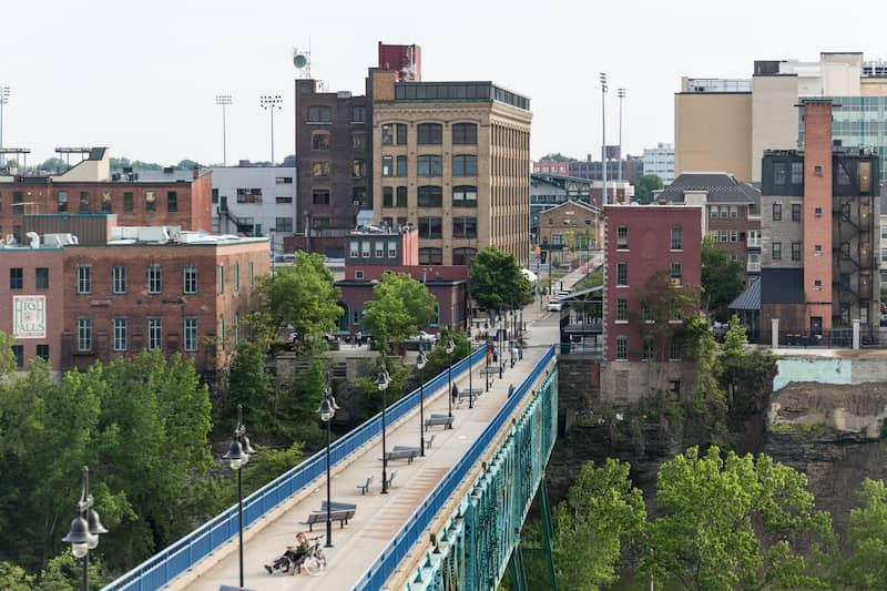 Large Blue Sidewalk Bridge With Vintage Brick Buildings