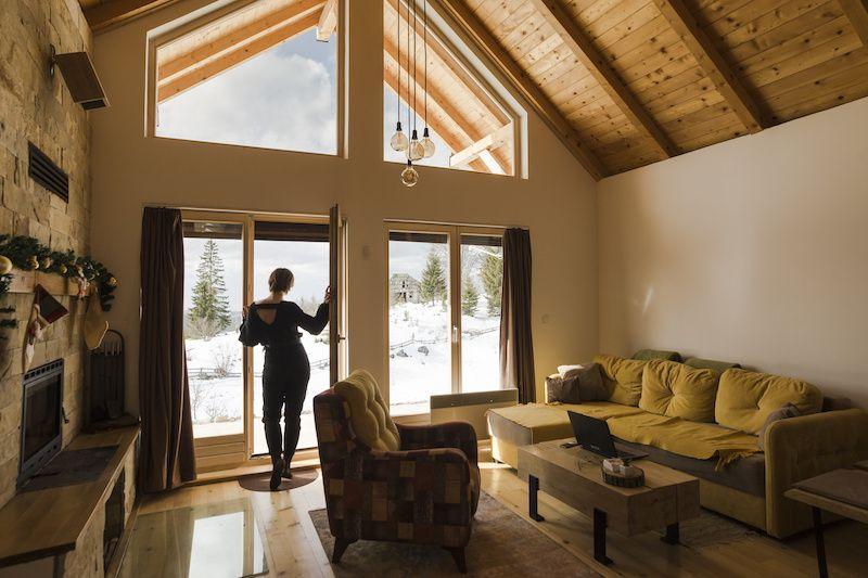 Woman standing in the doorway of an open cabin room.