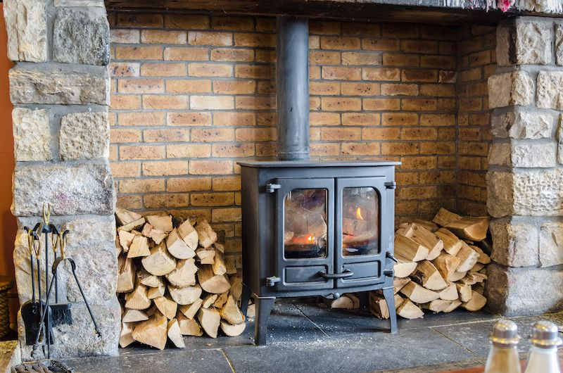 Wood burning stove with wood piles surrounding it.