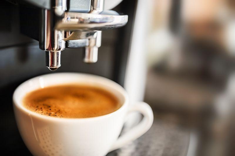 white coffee mug under an espresso machine