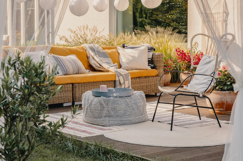 Terrace furniture: pouf used as a table, wicker couch and chair.