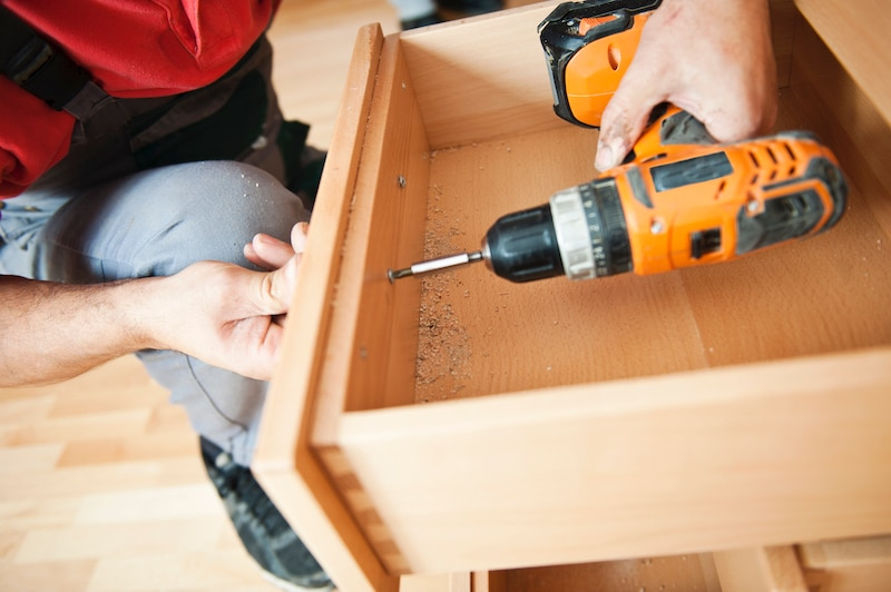 Person adding new hardware to cabinets and drawers.