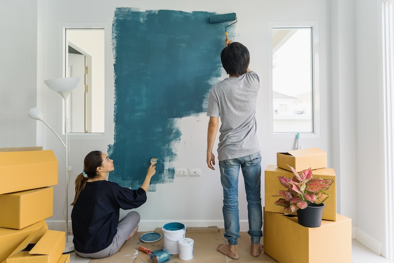 Young couple painting a wall together.