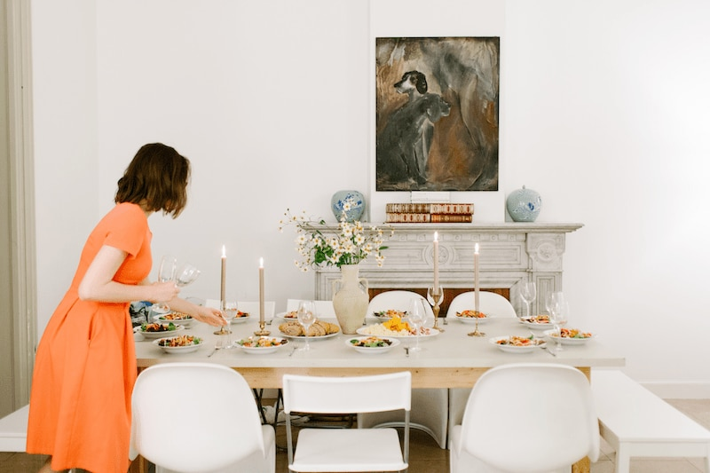 woman in orange dress decorating living room