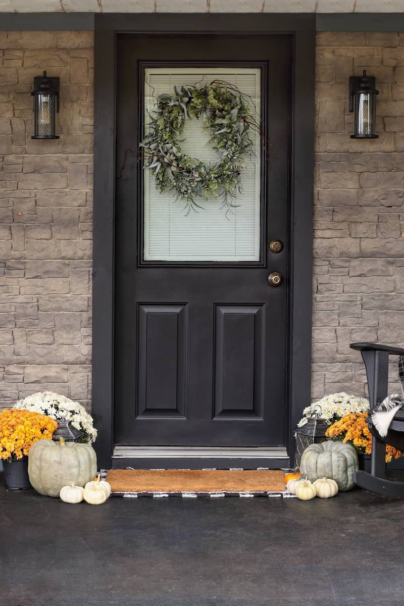 Grey front door with fall decor.