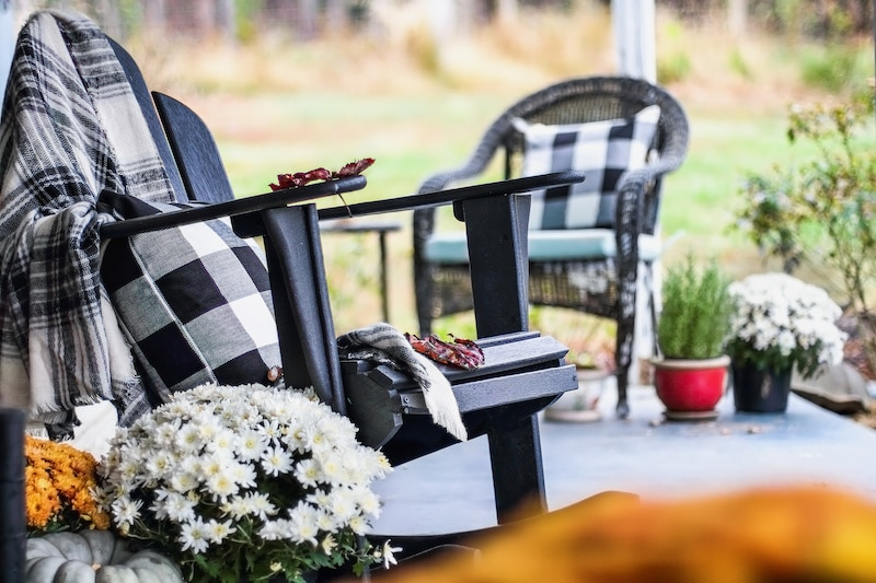 Mums and Adirondack chairs on a porch.