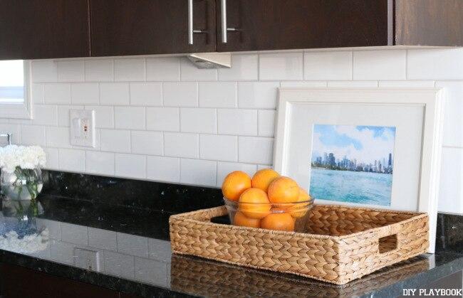white backsplash behind basket of oranges