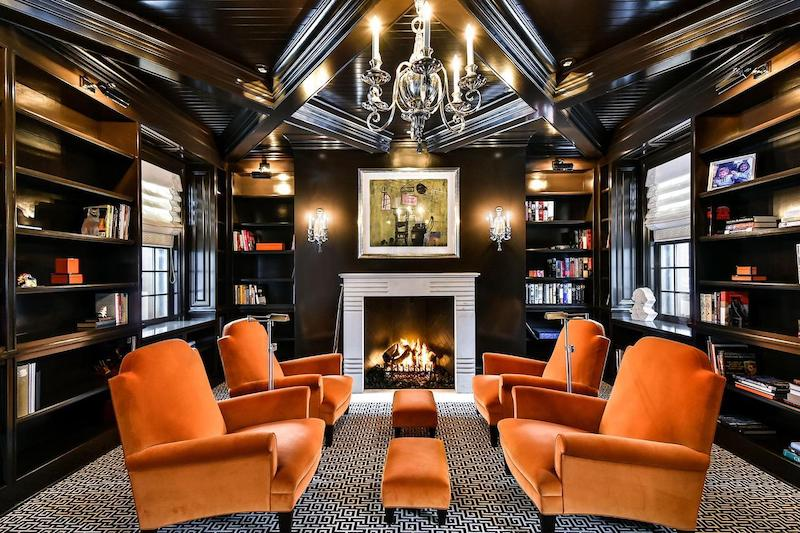 Luxury library with four velvet orange chairs and a chandelier.