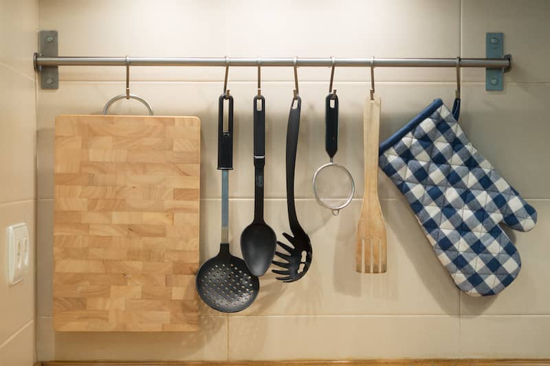 kitchen utensils. oven mitt, and cutting board hanging on rod in kitchen