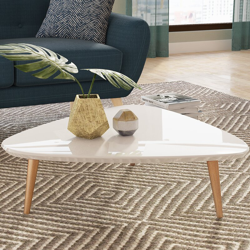 White coffee table with oak legs on a chevron rug