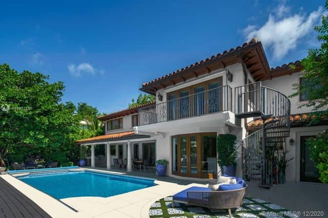 two story brown and white home with patio pool and large balcony