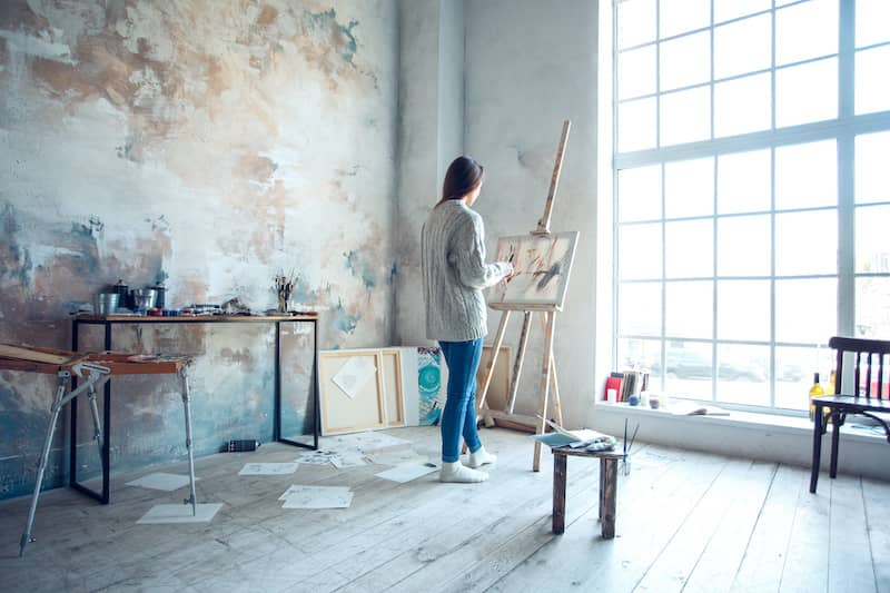 artist painting in bright studio