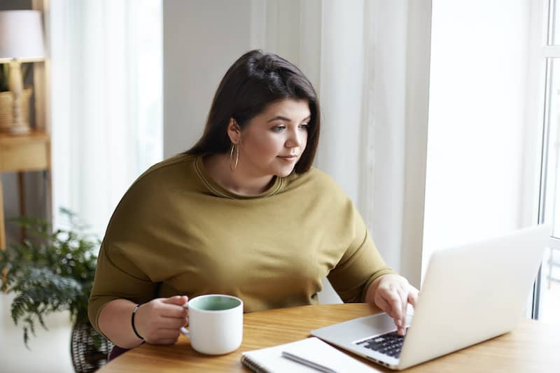 woman writing in shed with coffee