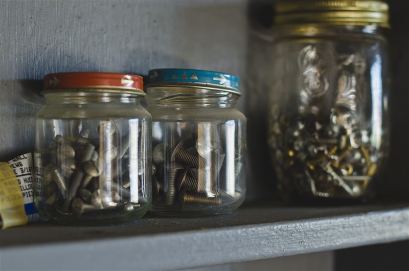 little nuts and bolts on a shelf in jars