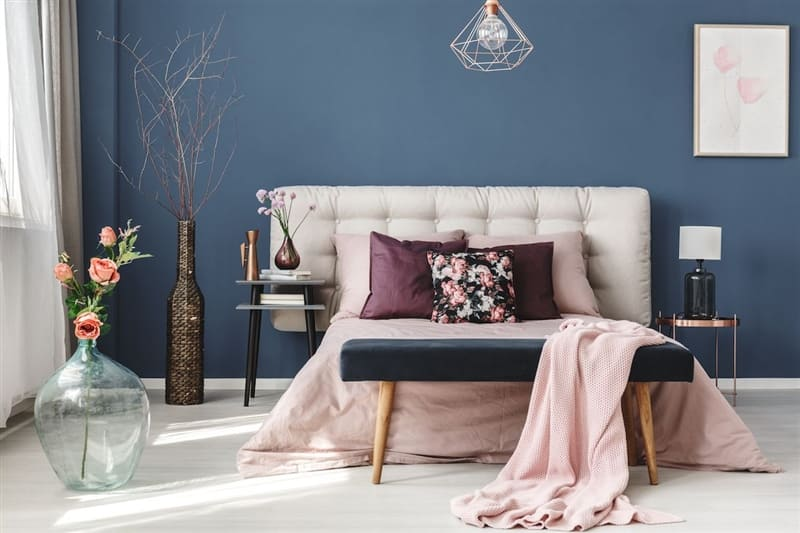 Bedroom with dark blue wall and pink bedding.