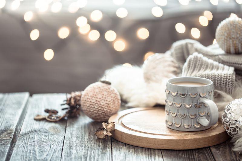 Boho Christmas decor with mug of coffee, shiny ornaments and cozy blankets.