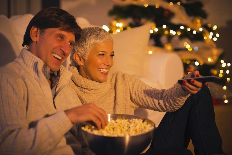 Couple watching movies near their Christmas tree.