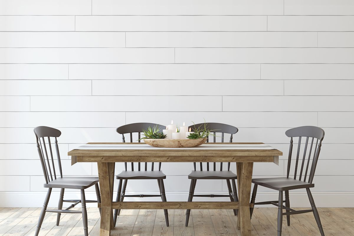 Wood dining table with four chairs and shiplap accent wall.