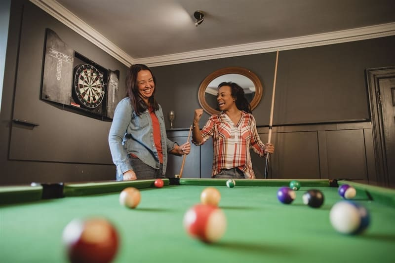 Two friends playing billiards in their basement.