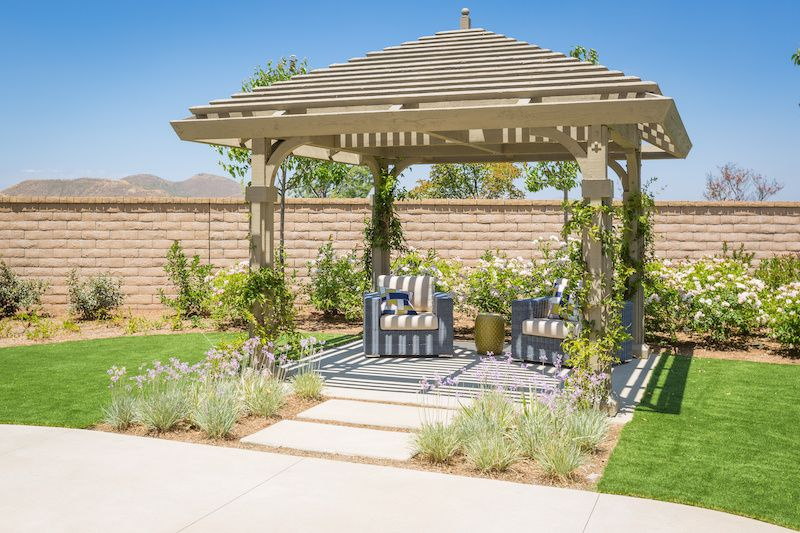 gabled pergola in a back yard with lush green grass