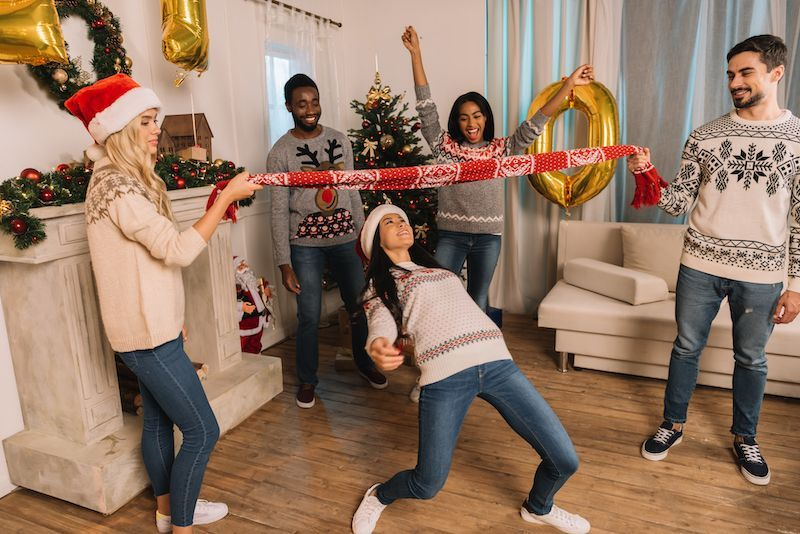 Group of friends doing the Limbo with a holiday scarf at a holiday party.