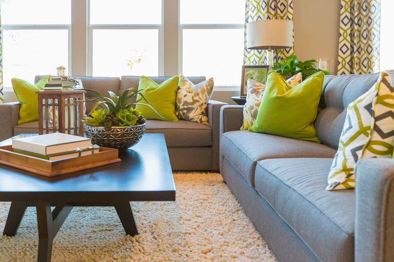 Living room with grey couches and green throw pillows